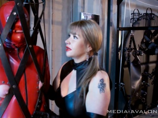 latex slave hangs in a leather strapcage