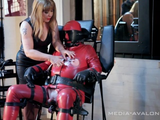 Latex slave is strapped on a bondage chair