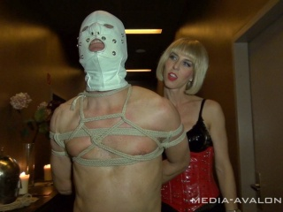 slave with a white leather mask in bondage