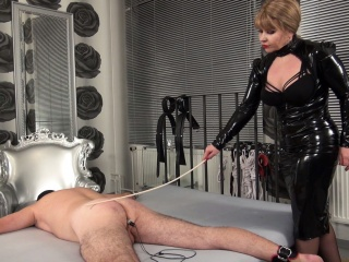 Mistress in black shiny vinyl dress is caning the ass of the slave