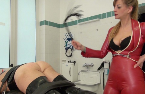mistress in a red latex dress is whipping the ass of her slave