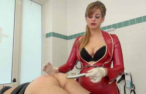 mistress in a red latex uniform is inserting the anal plug in the ass of her slave